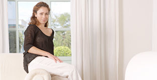 Mature woman sitting on sofa. Stock Photos