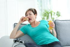 Mature woman sitting on sofa with hamburger, soda and videogame console. Sedentary lifestyle concept Stock Images