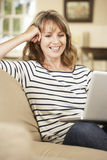 Mature Woman Sitting On Sofa At Home Using Laptop Stock Photo