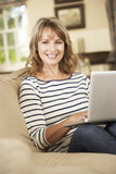 Mature Woman Sitting On Sofa At Home Using Laptop Royalty Free Stock Images