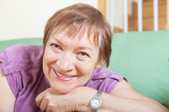 Mature woman  sitting on sofa  and smiling Stock Photography
