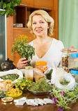 Mature woman sitting at  table with medicinal herbs Stock Photos