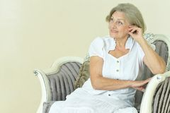 Mature woman sitting in vintage sofa Stock Photography