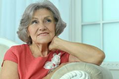 Mature woman sitting in vintage sofa Royalty Free Stock Image