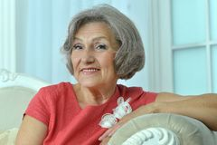 Mature woman sitting in vintage sofa Stock Images