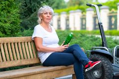 Mature woman sitting on wooden bench in summer stock photos