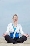 Mature woman sitting in yoga position at beach Stock Image