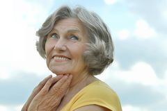 Mature woman on sky background Stock Photo