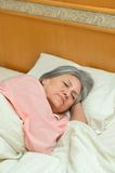 Mature woman sleeping in bed Royalty Free Stock Photos