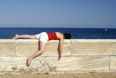 Mature woman sleeping on a wall Royalty Free Stock Photo