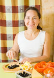 Mature woman slicing olive Stock Photography