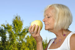 Mature woman smelling apple. Royalty Free Stock Images