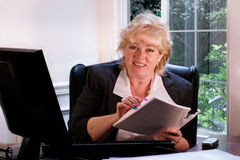 Mature woman smiles at her desk Royalty Free Stock Photo