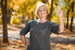 A mature woman smiles and makes selfie on the phone. In the autumn park. royalty free stock photography