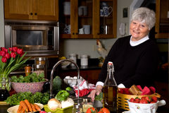 Mature woman smiling while cooking. Royalty Free Stock Image