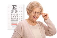 Mature woman smiling in front of an eye chart Stock Photo
