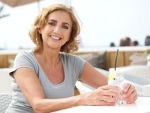Mature woman smiling with glass of water at restaurant Stock Photo