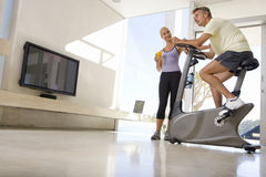Mature woman smiling at mature man riding stationary bicycle in living room, low angle view stock image