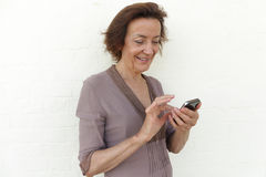 Mature woman smiling and texting. Mature woman with smartphone, smiling while checking her social media or texting Royalty Free Stock Photo