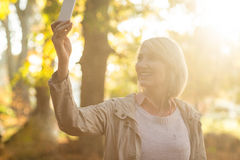 Mature woman smiling while using cellphone Royalty Free Stock Photos