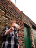 Mature Woman Smoking an Electronic Cigarette. A mature woman smokes an electronic cigarette outside in poor weather conditions stock photography