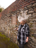 Mature Woman Smoking an Electronic Cigarette. A mature woman smokes an electronic cigarette outside in poor weather conditions royalty free stock images