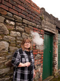 Mature Woman Smoking an Electronic Cigarette. A mature woman smokes an electronic cigarette outside in poor weather conditions stock photos
