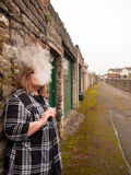 Mature Woman Smoking an Electronic Cigarette. A mature woman smokes an electronic cigarette outside in poor weather conditions royalty free stock photo