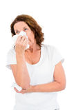 Mature woman sneezing while standing Royalty Free Stock Image