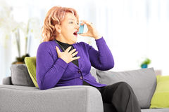 Mature woman on a sofa taking asthma treatment with inhaler at h Stock Images