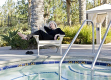Mature Woman by the Spa. Mature woman relaxing in a chair next to the spa Royalty Free Stock Photography