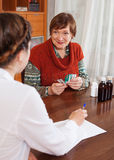 Mature woman speaking the doctor the symptoms Royalty Free Stock Photo