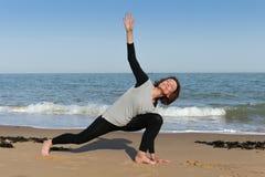 Mature woman sphinx yoga on the beach. Mature woman doing sphinx yoga pose on the beach Royalty Free Stock Photo