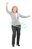 Mature woman spinning a hula hoop Stock Images