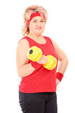 Mature woman in sportswear lifting a dumbbell Royalty Free Stock Photography