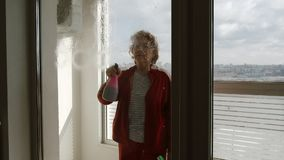 Mature woman sprays window cleaner on large window indoors - side view stock video footage