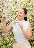 Mature woman in spring. Beautiful mature woman on background of the cherry blossoms stock image