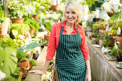 Mature woman standing amidst plants at greenhouse Stock Photos
