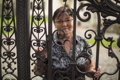 Mature woman standing behind a metal fence in the Park. Walking. Royalty Free Stock Images