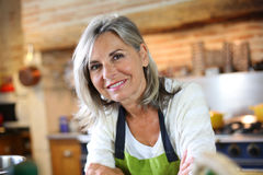 Mature woman standing in kitchen Royalty Free Stock Photos