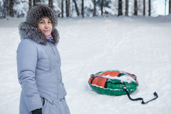 Mature woman standing near inflatable snow tube in winter forest Royalty Free Stock Image