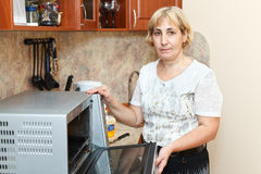 Mature woman standing near microwave Royalty Free Stock Photos
