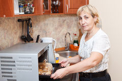 Mature woman standing near microwave Stock Image