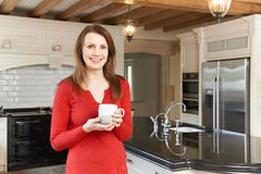 Mature Woman Standing In New Luxury Fitted Kitchen Stock Photography