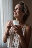 Mature woman standing at the window with a cup of tea Royalty Free Stock Image