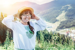 Mature woman stands on the top of the hill and enjoys the view Royalty Free Stock Photo