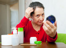 Mature woman stares on grizzled hair. In mirror at home Royalty Free Stock Photos