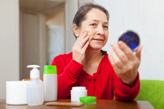 Mature woman stares on her face. In mirror at home Royalty Free Stock Image