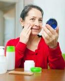 Mature woman stares to facial rhytid Stock Photos