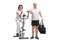 Mature woman on a stationary bike and a mature man with a sports. Mature women on a stationary bike and a mature men with a sports bag isolated on white Stock Photography